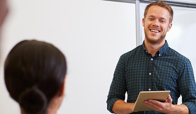 Smilende mand præsenterer for et publikum.