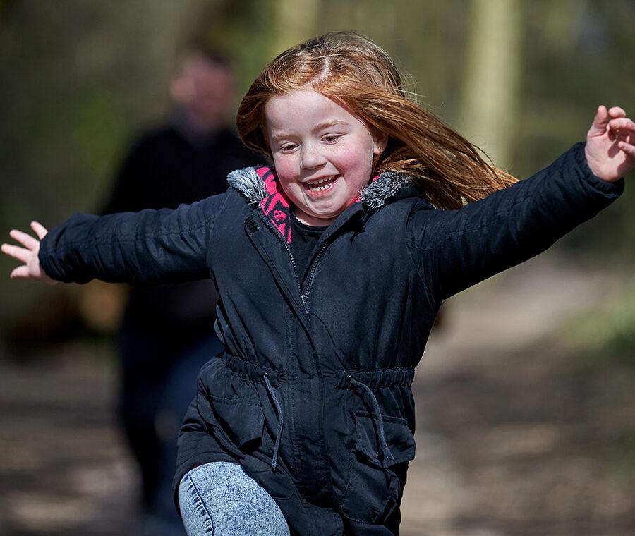 En lille rødhåret pige hopper glad af sted i skoven