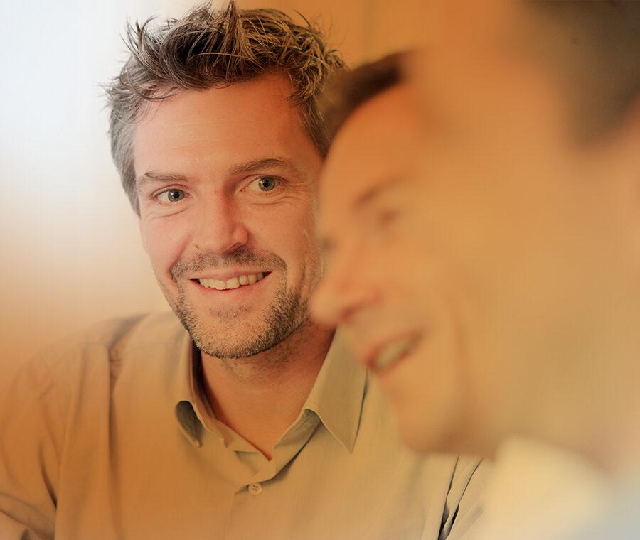 Et billede af personer, der snakker sammen - kun en er i fokus.