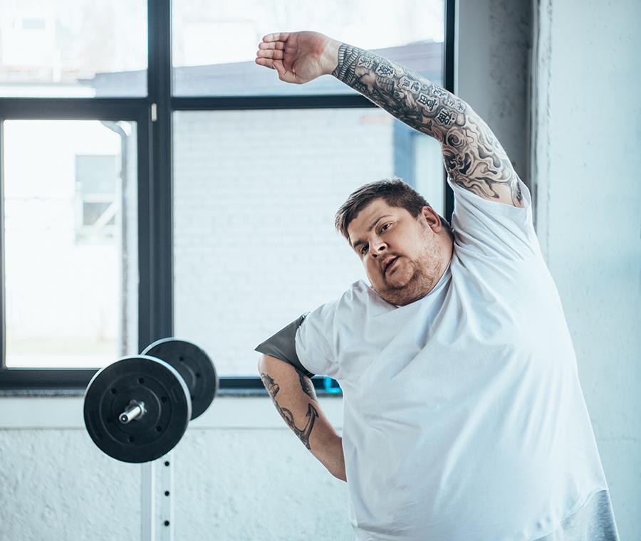 Billedet viser en mand, der laver strækøvelser i et træningsrum.