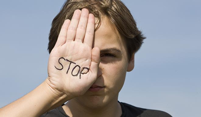 Dreng holder en hånd frem, hvorpå der står stop.