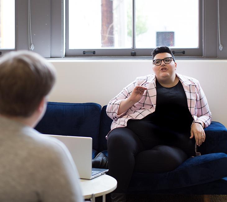 To personer med overvægt i gang med en samtale i et lyst rum med store vinduer.