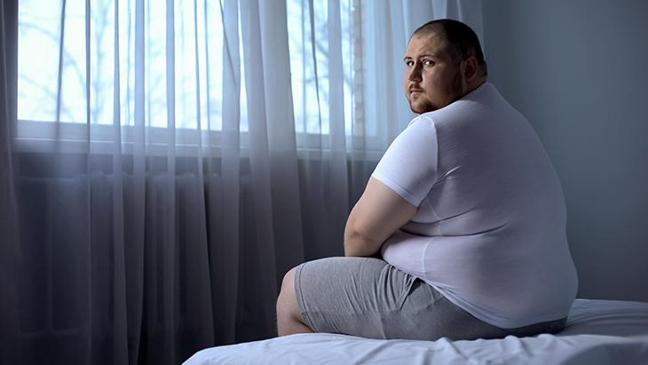 Mand med overvægt sidder på en seng og ser trist ud, mens han kigger direkte ind i kameraet.